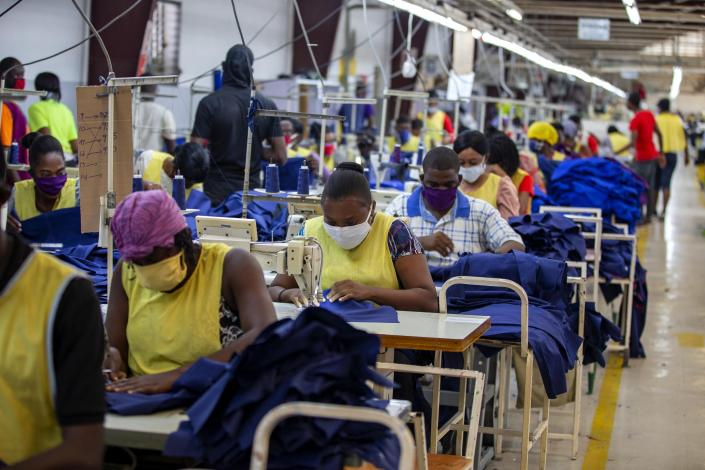 FILE - In this April 21, 2020 file photo, factory workers sew medical clothing and face masks at the Sonapi Industrial Park in Port-au-Prince, Haiti. The textile factory re-opened as part of a government financed effort to provide protective gear to medical workers amid the new coronavirus pandemic. (AP Photo/Dieu Nalio Chery, File)