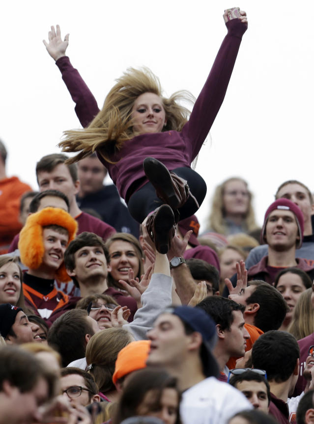 A Virginia Tech fan is tossed up as they celebrate a touchdown during the first half of an NCAA college football game against Maryland in Blacksburg, Va., Saturday, Nov. 16, 2013. (AP Photo/Steve Helber)