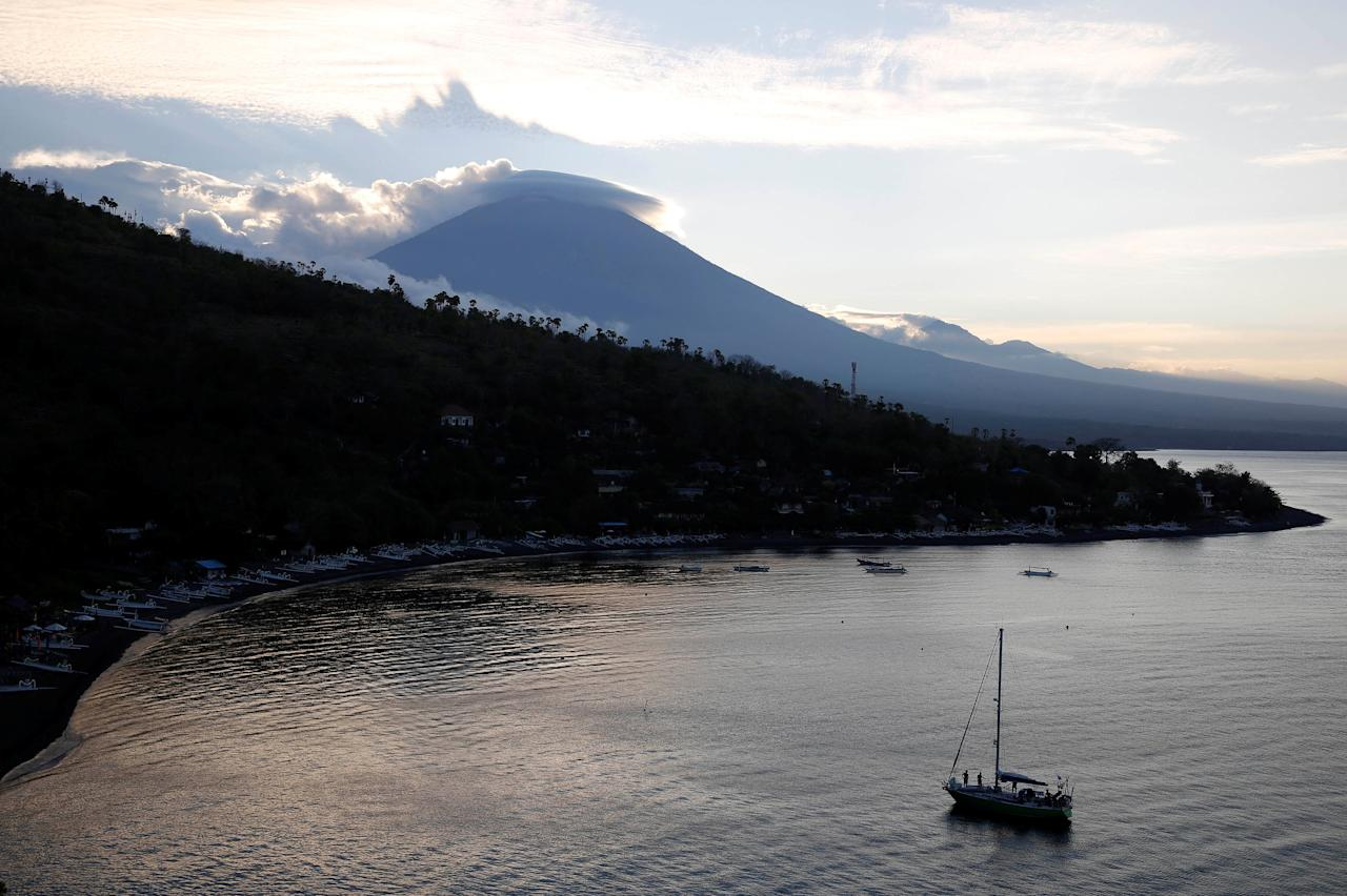 <p>A sailboat is seen at the sun sets behind Mount Agung, a volcano on the highest alert level, in Amed on the resort island of Bali, Indonesia on Sept. 25, 2017. (Photo: Darren Whiteside/Reuters) </p>