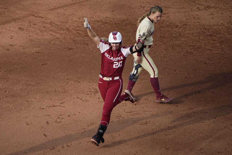 Oklahoma's Jana Johns (20) celebrates as she runs past Florida State's Josie Muffley, right, on a home run during the third inning of in the second game of the NCAA Women's College World Series softball championship series Wednesday, June 9, 2021, in Oklahoma City. (AP Photo/Sue Ogrocki)
