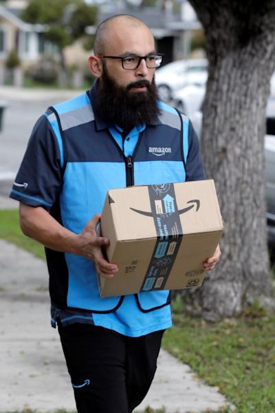 Danny Gonzalez walks with a package when he delivers for Amazon during the outbreak of the coronavirus disease