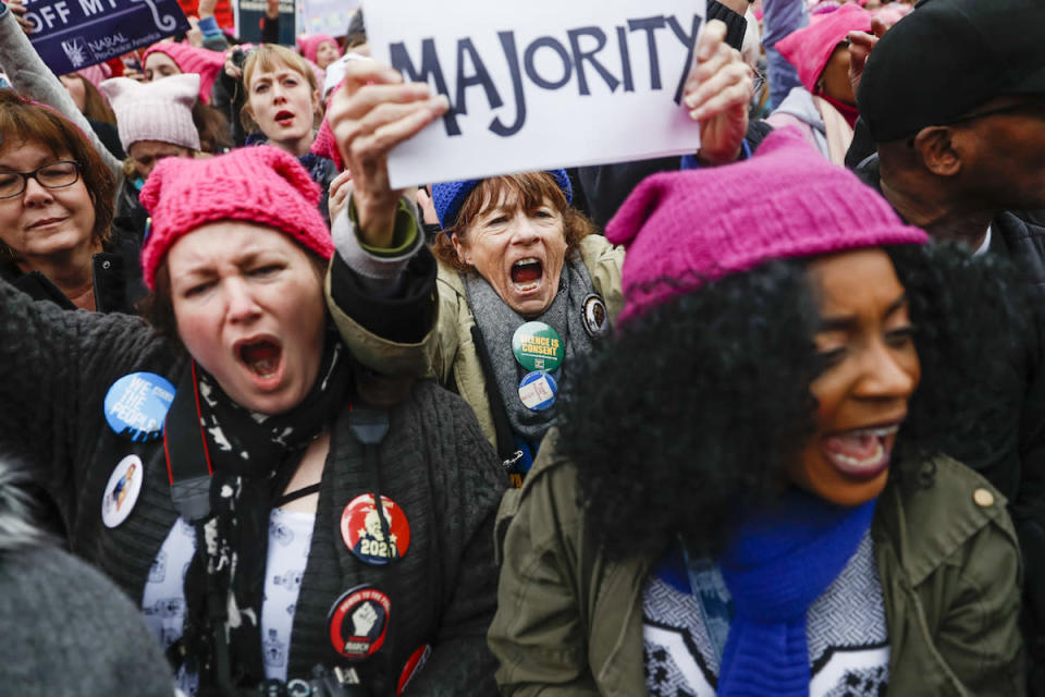 <p>In addition to hats, people hold signs, wear pins, and cheer loudly. (Photo: John Minchillo/AP) </p>