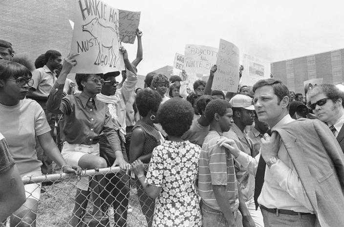 File - In this May 21, 1970, file photo, U.S. Sen. Birch Bayh, D-Ind., right, passes demonstrators protesting the slaying of two African Americans on the campus of Jackson State College, in Jackson, Miss. Sen. Bayh and several other congressmen inspected the site where two men died and 12 people were wounded as white lawmen shot indiscriminately, riddling the windows of a women's dormitory as officers claimed they had seen a sniper. The historically Black school canceled its 1970 commencement after the incident. Fifty-one years later, the school now called Jackson State University is honoring its Class of 1970, as members are being invited back to salute their academic achievements with a graduation ceremony. Saturday, May 15, 2021. (AP Photo, File)