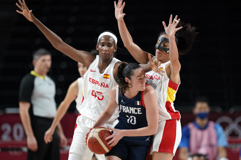 France's Sarah Michel (10) looks to pass around Spain's Astou Ndour (45) and Cristina Ouvina, right, during a women's basketball quarterfinal round game at the 2020 Summer Olympics, Wednesday, Aug. 4, 2021, in Saitama, Japan. (AP Photo/Eric Gay)
