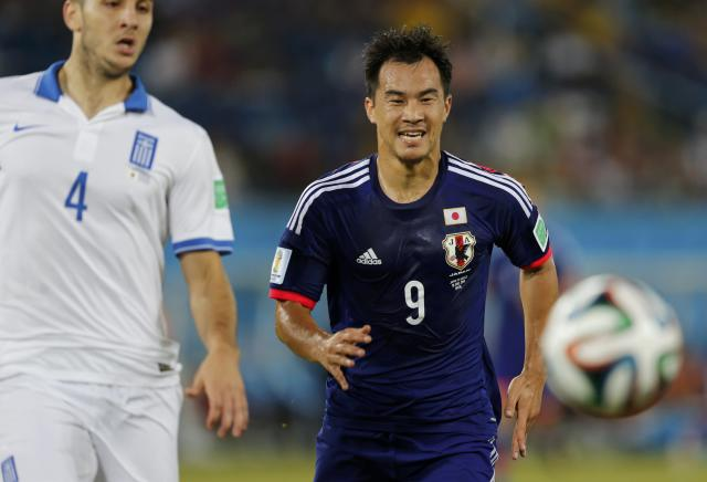 Japan's Shinji Okazaki runs for the ball ahead of Greece's Kostas Manolas during their 2014 World Cup Group C soccer match at the Dunas arena in Natal June 19, 2014. REUTERS/Sergio Moraes (BRAZIL - Tags: SOCCER SPORT WORLD CUP)