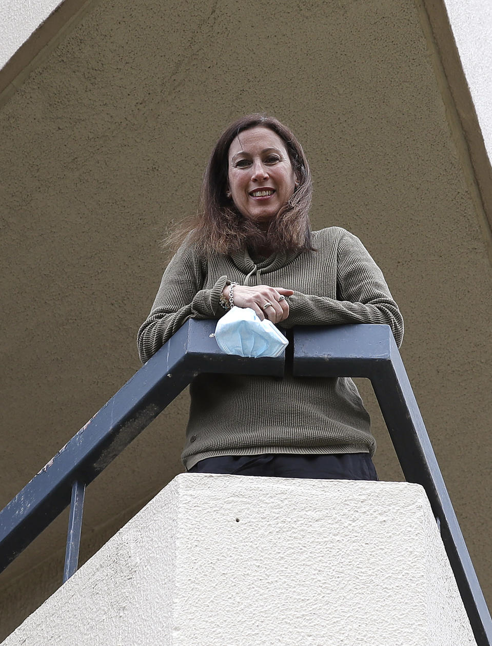 U.S. citizen Michelle Parker poses for a photo on the balcony at her home in Sydney on Oct. 20, 2020. Parker is a flight attendant and Australia considers her an essential worker who flies between her Sydney home and San Francisco. But New South Wales state's added layer of strict quarantine rules meant that when she was returning to her husband and children in Sydney for days, she was no longer considered an essential worker but a traveler who was expected to pay 3,000 Australian dollars ($2,100) to quarantine in a Sydney hotel for two weeks. (AP Photo/Rick Rycroft)