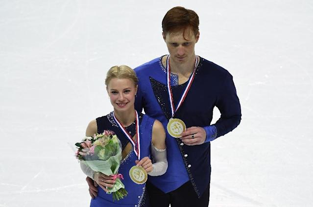 Russian's Evgenia Tarasova and Vladimir Morozov celebrate after winning the senior pairs skating at the ISU Grand Prix of figure skating Final, on December 9, 2016 in Marseille, southern France (AFP Photo/ANNE-CHRISTINE POUJOULAT)