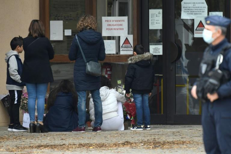 People place flowers at the doors of a Paris school where the beheaded teacher worked