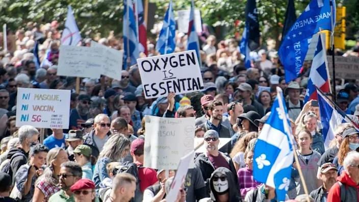 Some demonstrators in Montreal on Saturday carried signs and wore T-shirts and hats denouncing what they called fear campaigns by the Quebec government, suggesting that the danger of COVID-19 has been overstated. (Graham Hughes/The Canadian Press)