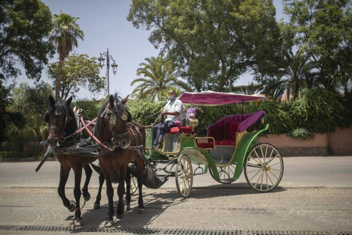 Mohammed El Garbouh, a horse carriage owner, waits for customers in the landmark Jemma el-Fnaa in Marrakech, Morocco, Wednesday, July 22, 2020. Morocco's restrictions to counter the coronavirus pandemic have taken a toll on the carriage horses in the tourist mecca of Marrakech. Some owners struggle to feed them, and an animal protection group says hundreds of Morocco's horses and donkeys face starvation amid the collapsing tourism industry. (AP Photo/Mosa'ab Elshamy)