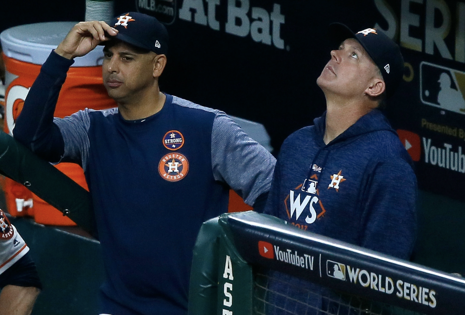 Bench coach Alex Cora #26 and manager A.J. Hinch #14 of the Houston Astros look on from the dugout during the fifth inning against the Los Angeles Dodgers in game five of the 2017 World Series at Minute Maid Park on October 29, 2017 in Houston, Texas. (Photo: Bob Levey/Getty Images)
