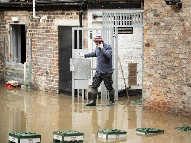 A man navigates flood water in York after the River Ouse burst its banks, as a third consecutive weekend of stormy weather is bringing further flooding misery to already sodden communities: PA