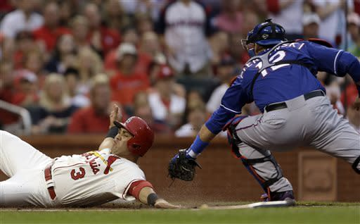 St. Louis Cardinals' Carlos Beltran, left, scores ahead of the tag from Texas Rangers catcher A.J. Pierzynski, right, on a single by Allen Craig during the first inning of a baseball game on Saturday, June 22, 2013, in St. Louis. (AP Photo/Jeff Roberson)