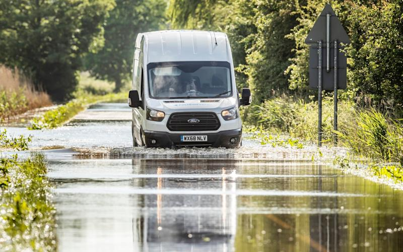 A van drives through floodwater in Wainfleet All Saints, in Lincolnshire, where streets and properties flooded - PA