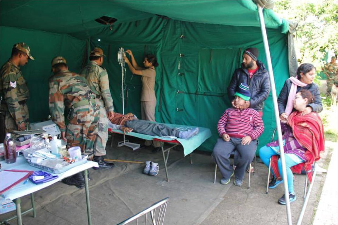 """In this photograph received from the Indian Army on June 20, 2013, members of the Indian Defence Forces tend to patients at a field hospital following flash floods in the northern Uttarakhand state. India's military battled on June 20 to reach villages and towns cut off by flash floods and landslides in the country's north as officials warned at least 1,000 people may have been killed. AFP PHOTO/INDIAN ARMY   ----EDITORS NOTE---- RESTRICTED TO EDITORIAL USE - MANDATORY CREDIT -  """"AFP PHOTO/INDIAN ARMY"""" - NO MARKETING NO ADVERTISING CAMPAIGNS - DISTRIBUTED AS A SERVICE TO CLIENTS -----"""