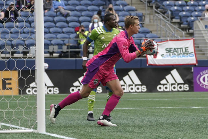 Seattle Sounders goalkeeper Stefan Cleveland, right, makes a stop against Atlanta United during the first half of an MLS soccer match, Sunday, May 23, 2021, in Seattle. (AP Photo/Ted S. Warren)