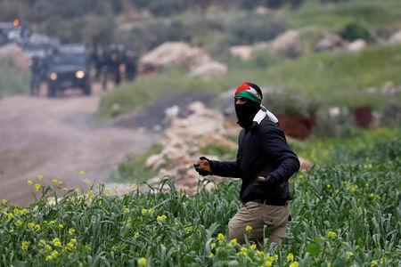 A Palestinian demonstrator runs during clashes with Israeli troops at a protest marking the Land Day, in al-Mughayer village in the Israeli-occupied West Bank March 29, 2019. REUTERS/Mohamad Torokman