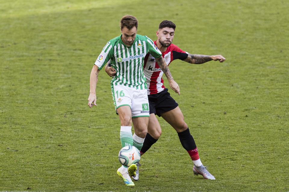 BILBAO, SPAIN - JUNE 20: Lorenzo Moron of Real Betis (L) fights for the ball with Unai Nuñez of Athletic Bilbao (R) during the Liga match between Athletic Club and Real Betis Balompie at San Mames Stadium on June 20, 2020 in Bilbao, Spain. Football Stadiums around Europe remain empty due to the Coronavirus Pandemic as Government social distancing laws prohibit fans inside venues resulting in all fixtures being played behind closed doors. (Photo by Ricardo Nogueira/Eurasia Sport Images/Getty Images)
