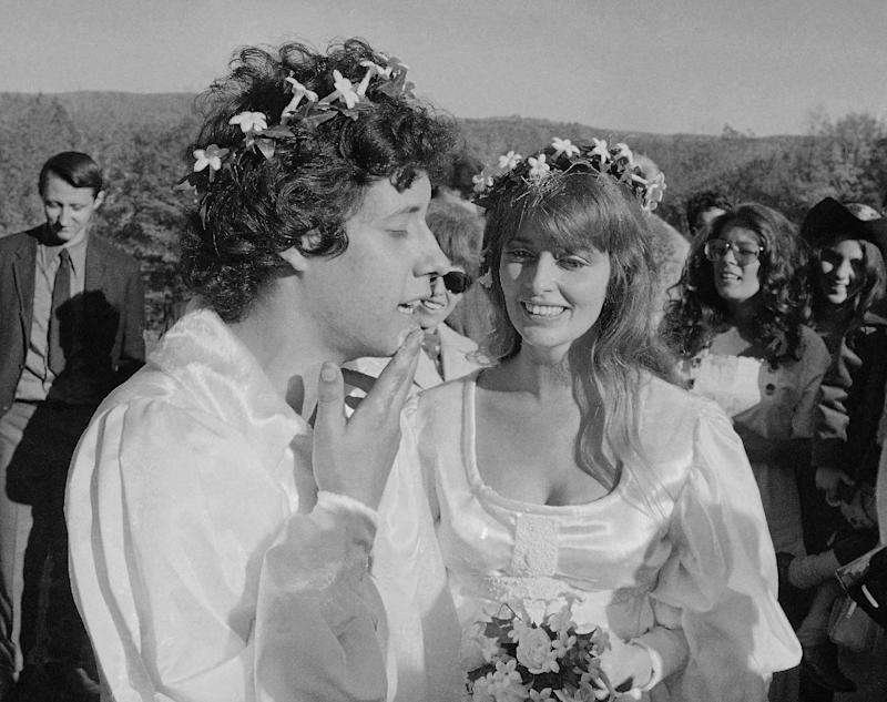 """FILE - This Oct. 9, 1969 file photograph shows performer Arlo Guthrie singing """"Amazing Grace"""" to his new bride Jackie Hyde, at their wedding ceremony on Guthrie's farm in Washington, Mass. Folk singer Arlo Guthrie has announced the death of his wife Jackie at age 68. An obituary released by Guthrie's record label says Jackie Guthrie had inoperable cancer and died Sunday, Oct. 14, 2012, at the couple's winter home in Sebastian, Fla. They had recently celebrated their 43rd wedding anniversary. (AP Photo/Steve Starr, file)"""
