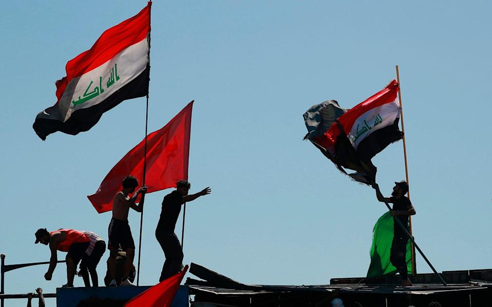 Anti-government protesters sit-in on barriers set up by security forces in Iraq - AP