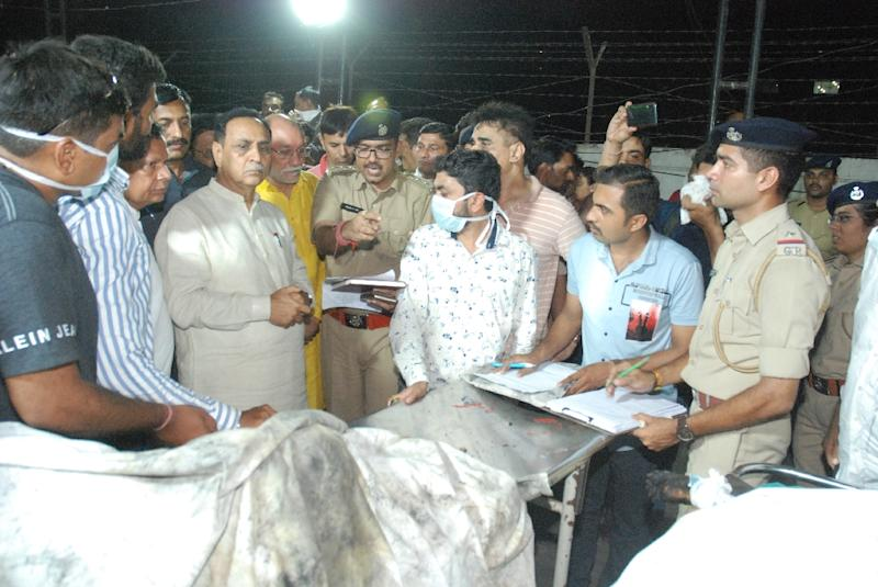 Gujarat Chief Minister Vijaybhai Rupani stands near the bodies of students who died in the fire in Surat (AFP Photo/STR)