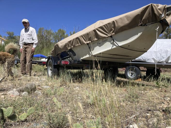 Tom Wiersema, who has been trout fishing on the upper North Platte River in Wyoming since the 1970s, stand by his drift boat near Encampment,Wyoming on Tuesday,Aug. 24, 2021. Low water caused Wiersema to stop fishing by boat on a long stretch of the river earlier than usual this year, lest he have to drag his boat over rocks. The upper North Platte is one of several renowned trout streams affected by climate change, which has brought both abnormally dry, and sometimes unusually wet, conditions to the western U.S. (AP Photo/Mead Gruver)