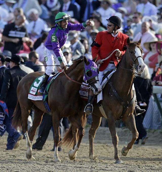 Victor Espinoza celebrates after riding California Chrome to a victory during the 140th running of the Kentucky Derby horse race at Churchill Downs Saturday, May 3, 2014, in Louisville, Ky. (AP Photo/Darron Cummings)