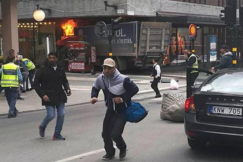 Onlookers flee the scene as a lorry crashed into a Stockholm department store