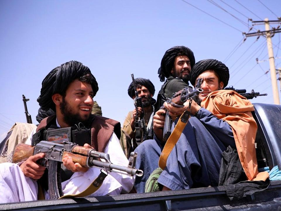 Taliban fighters outside the Hamid Karzai airport in Kabul as they celebrate victory.  (REUTERS)