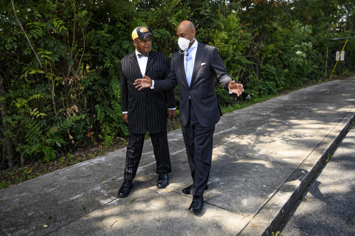 Tennessee State Rep. Harold Love, Jr., right, talks to fellow reverend Anthony Thomas as they stroll past their church which is situated next to I-40 on the other sideof the trees, Monday, July, 19, 2021, on the north side of Nashville, Tenn. Love Jr.'s father, a Nashville city councilman, was forced to sell his family home nearby to make way for the highway, but put up a fight in the 1960s against the rerouting of Interstate 40 because he believed it would stifle and isolate Nashville's Black community. Love Jr. is now part of a group pushing to build a cap across the highway that creates a community space to help reunify the city. (AP Photo/John Amis)