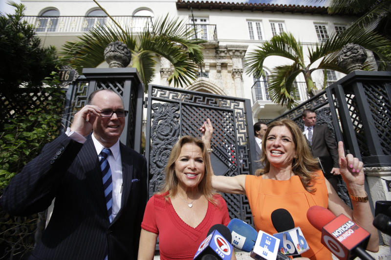 Realtors Jill Hertzberg, right, and Jill Eber, center, celebrate as they speak to the members of the media along side Lamar Fisher, left, of Fisher Auction Co., after the South Beach mansion that once belonged to Gianni Versace, rear, was sold for the winning bid of $41.5 million during an auction, Tuesday, Sept. 17, 2013 in Miami Beach, Fla. VM South Beach LLC, who's principals include the Nakash family of New York, who control Jordache Enterprises had the winning bid. Gianni Versace bought the property in 1992. He was fatally shot on its steps in 1997 by a serial killer. His family sold it in 2000, and it operated as a private club and then as a boutique hotel until earlier this year. (AP Photo/Wilfredo Lee)