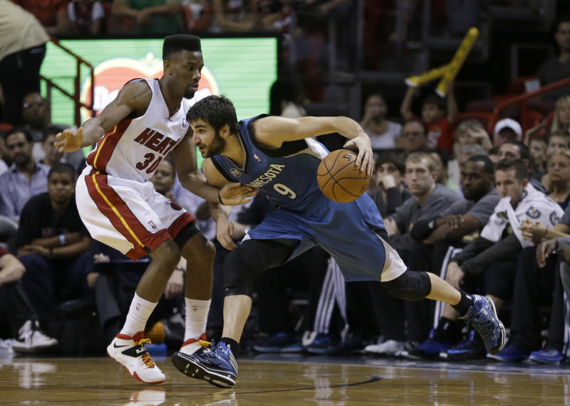 Minnesota Timberwolves guard Ricky Rubio (9) drives around Miami Heat guard Norris Cole (30) during the first half of an NBA basketball game in Miami, Friday, April 4, 2014. (AP Photo/Alan Diaz)