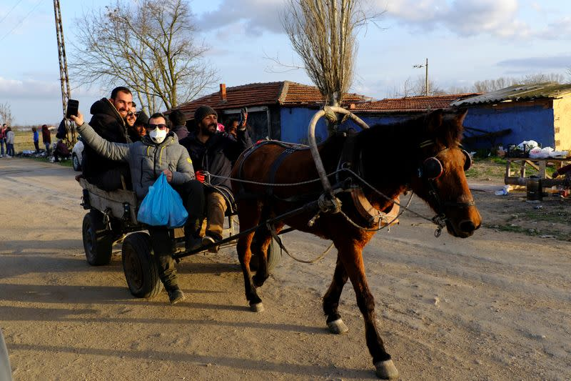 Migrants are transported by locals on a horse cart towards Turkey's Pazarkule border crossing with Greece's Kastanies, in Edirne