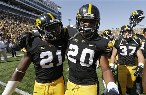 Iowa defensive back Nico Law (21) and linebacker Christian Kirksey (20) celebrate after their 31-13 victory over Minnesota in an NCAA college football game, Saturday, Sept. 29, 2012, in Iowa City, Iowa. Kirksey returned an interception 68-yards for a touchdown for Iowa in the second half. (AP Photo/Charlie Neibergall)