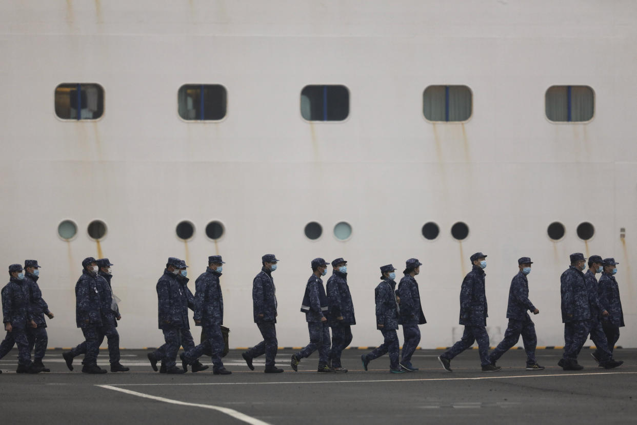 Members of Japan Self-Defense Forces walk past the quarantined Diamond Princess cruise ship Sunday, Feb. 16, 2020, in Yokohama, near Tokyo. The U.S. says Americans aboard a quarantined ship will be flown back home on a chartered flight Sunday, but that they will face another two-week quarantine. (AP Photo/Jae C. Hong)