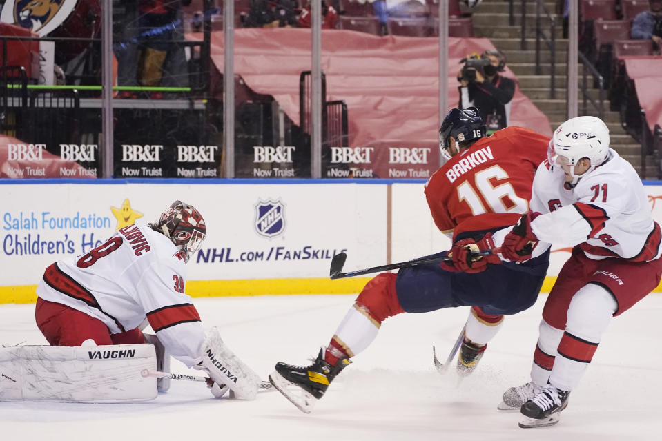 Florida Panthers center Aleksander Barkov (16) attempts a shot at Carolina Hurricanes goaltender Alex Nedeljkovic (39) and right wing Jesper Fast (71) during the second period of an NHL hockey game, Monday, March 1, 2021, in Sunrise, Fla. (AP Photo/Wilfredo Lee)