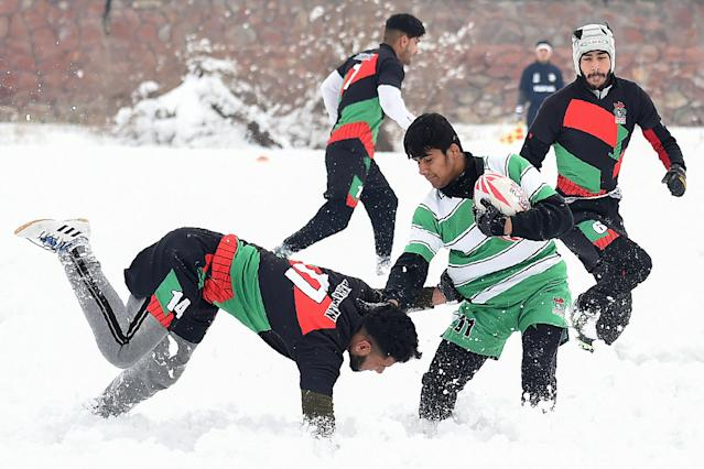 "Players compete for the ball during a ""snow rugby"" tournament in a field after snowfall in Kabul on January 13, 2020. (Photo by WAKIL KOHSAR/AFP via Getty Images)"