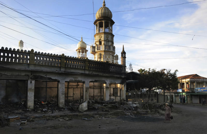 In this May 29, 2013 photo, Ma Sandar Soe, right in foreground, walks towards the remains of her burned shop in front of a vandalized mosque in Lashio, northern Shan State, Myanmar. When a huge mob of Buddhist thugs crawled on the roof of Ma Sandar Soe's shop, doused it with gasoline and set it ablaze, the Buddhist businesswoman didn't blame them for burning it to the ground despite seeing it happen with her own eyes. Instead, her wrath was reserved for minority Muslims she accused of igniting Myanmar's latest round of sectarian unrest. (AP Photo/Todd Pitman)