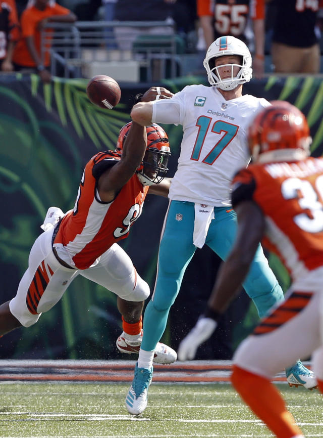 FILE - In this Oct. 7, 2018, file photo, Miami Dolphins quarterback Ryan Tannehill (17) fumbles the ball as he's hit by Cincinnati Bengals defensive end Carlos Dunlap (96) during the second half of an NFL football game, in Cincinnati. The Bengals recovered the ball and returned it for a touchdown. Tannehill has been taking a pounding. He and the Dolphins will try and regroup for Sunday's game against Chicago. (AP Photo/Gary Landers, File)
