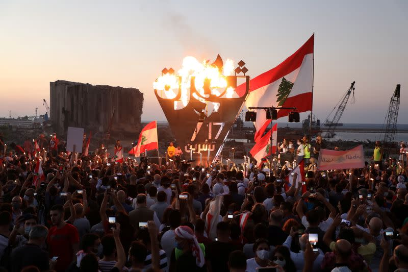 """Anti-government demonstrators take pictures of a metal sculpture spelling out the word """"revolution"""" topped by flames during a protest as Lebanese mark one year since the start of nation-wide protests, near Beirut's port"""