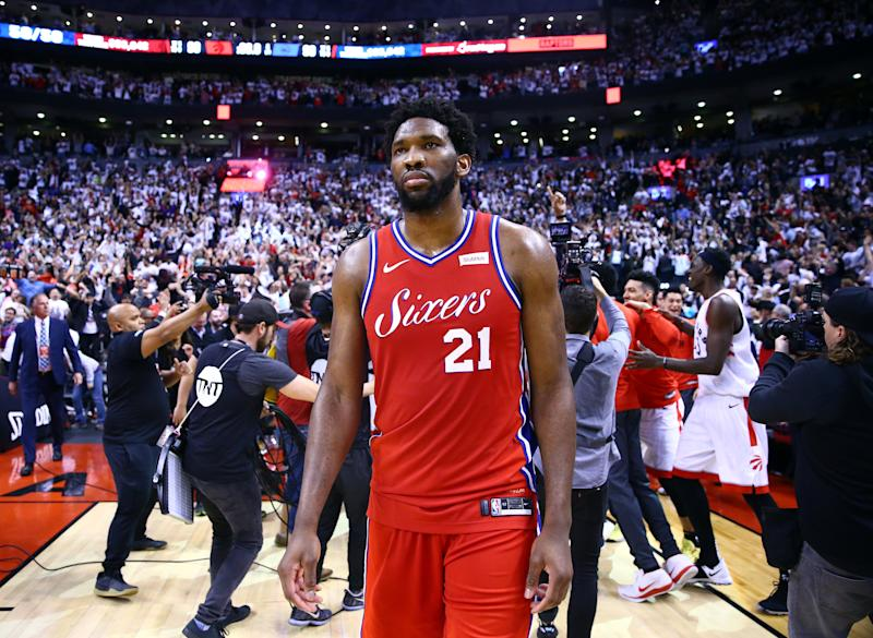 TORONTO, ON - MAY 12: Joel Embiid #21 of the Philadelphia 76ers looks on as Kawhi Leonard #2 of the Toronto Raptors celebrates with teammates after sinking a buzzer beater to win Game Seven of the second round of the 2019 NBA Playoffs at Scotiabank Arena on May 12, 2019 in Toronto, Canada. NOTE TO USER: User expressly acknowledges and agrees that, by downloading and or using this photograph, User is consenting to the terms and conditions of the Getty Images License Agreement. (Photo by Vaughn Ridley/Getty Images)