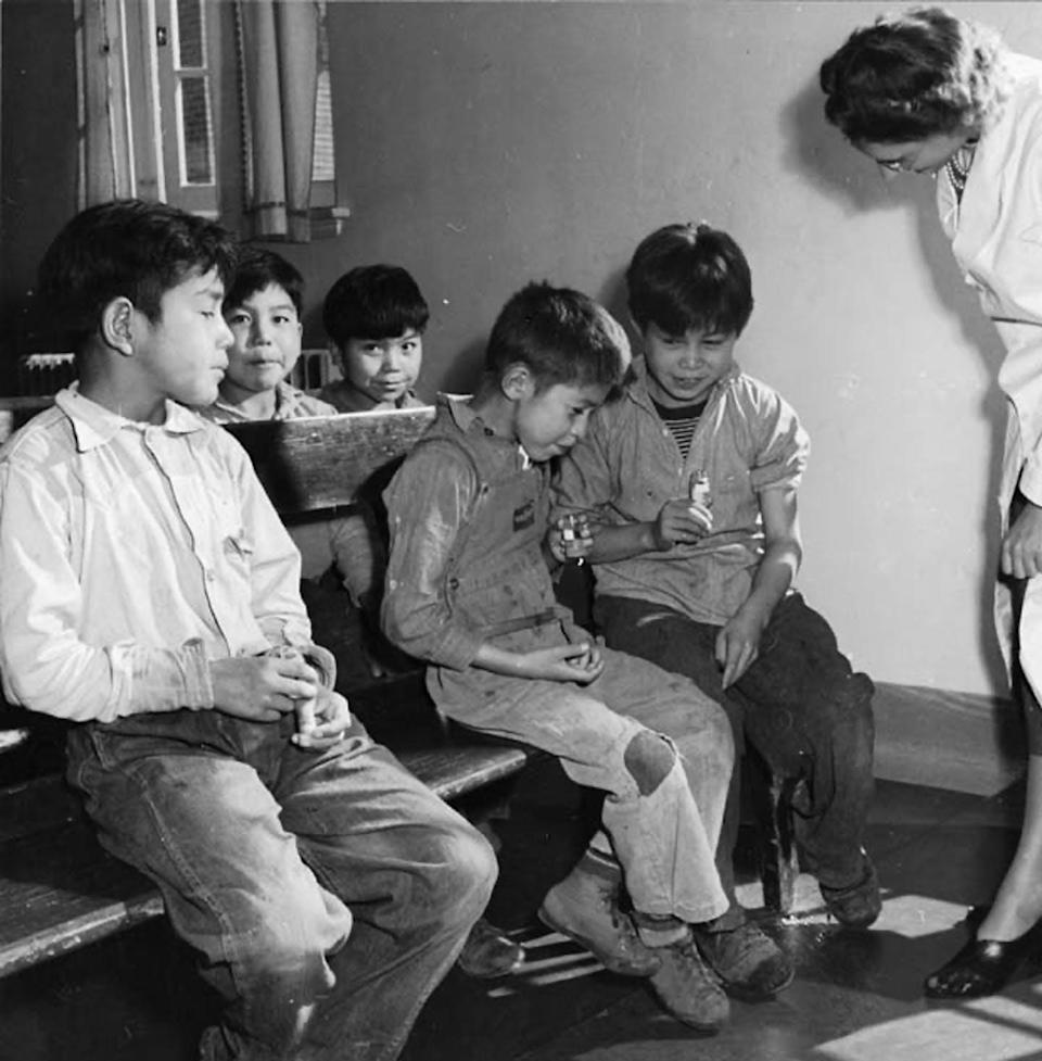 A nurse watches as boys spit into test tubes