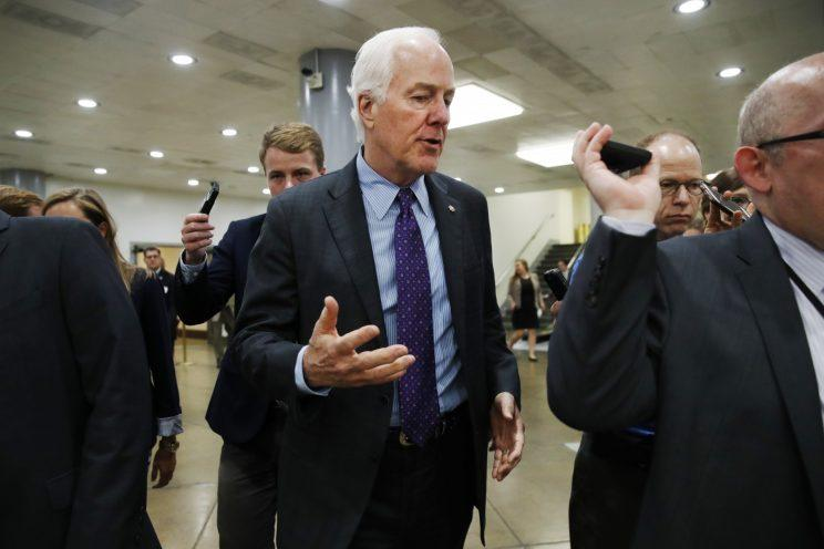 Senate Majority Whip John Cornyn of Texas, center, is pursued by reporters on Capitol Hill in Washington on July 11, 2017. (Photo: Jacquelyn Martin/AP)