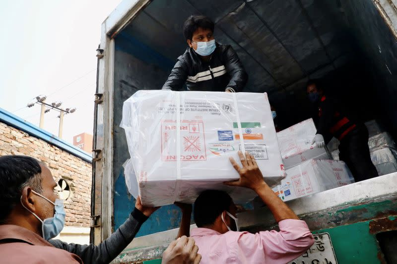 Workers unload a pickup van that carries Oxford-Astrazeneca COVID-19 vaccines which arrived from India as a gift to Bangladesh, in Dhaka
