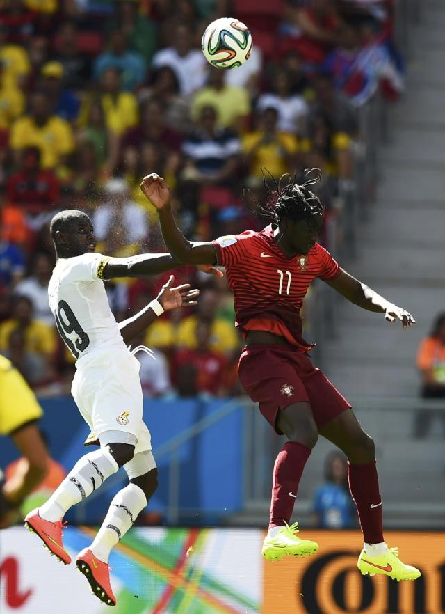 Ghana's Jonathan Mensah (L) and Portugal's Eder jump for the ball during their 2014 World Cup Group G soccer match at the Brasilia national stadium in Brasilia June 26, 2014. REUTERS/Dylan Martinez (BRAZIL - Tags: SOCCER SPORT WORLD CUP)