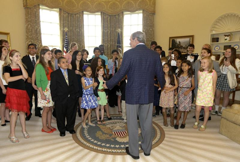 Former President George W. Bush, center, surprises 43 Dallas-Fort Worth area school children in the replica of the oval office at the Bush Presidential Library Wednesday, May 1, 2013, in Dallas. The students were the first official guest of the museum on its' opening day. (AP Photo/Tony Gutierrez)