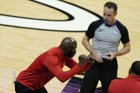 Atlanta Hawks head coach Lloyd Pierce, left, talks with official Josh Tiven, right, during the second half of an NBA basketball game against the Miami Heat, Sunday, Feb. 28, 2021, in Miami. (AP Photo/Lynne Sladky)