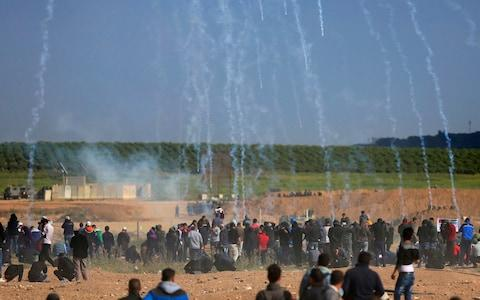 Teargas canisters fired by Israeli troops fall down on Palestinians during a demonstration near the Gaza Strip border - Credit: AP