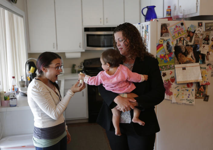 In this Sept. 26, 2012 picture, Sabina Widmann, right, holds her baby girl Stella while domestic worker Alicia Wotherspoon, left, holds a bannana before work at their home in San Diego. (AP Photo/Gregory Bull)