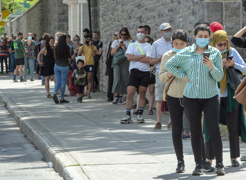 Hundreds of people lineup at the COVID-19 testing clinic Tuesday, July 14, 2020 in Montreal. The city has recommended that anyone who has been in a bar since July 1, 2020 to get tested. (Ryan Remiorz/The Canadian Press via AP)